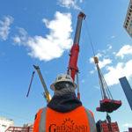 Greenland Enterprises employee back watching crane lifting equipment