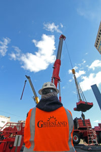 Greenland Enterprises employee back watching crane lifting equipment