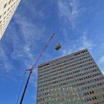 street view of crane lifting HVAC equipment onto a skyscraper
