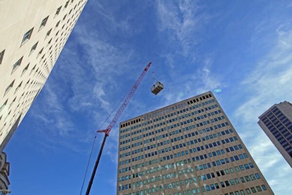 street view of crane lifting HVAC equipment onto a skyscraper