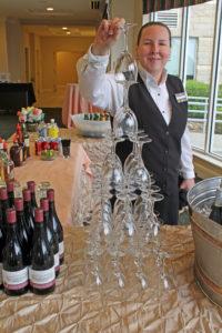 hotel employee stacking wine glasses