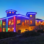 two story home with colored light accents at dusk