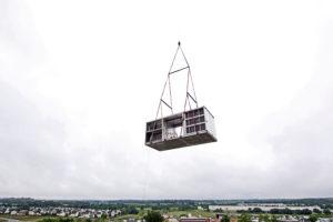 crane lifting HVAC equipment onto roof