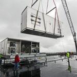 crane lifting HVAC equipment on roof