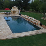 backyard pool in wooded yard with outdoor fireplace