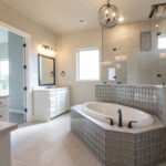 master bath tub in center with walk-in shower behind and his and hers vanities