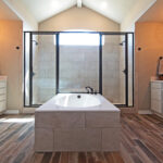master bath center tub with walk-in shower at far end and his and hers vanities
