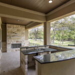 outdoor bar and fireplace with wooded backyard