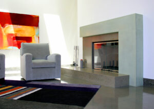 modern stained concrete fireplace with abstract art and easy chair