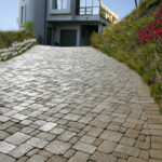 paved stone driveway leading to two-story house