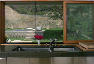 stained concrete kitchen counter with window overlooking backyard