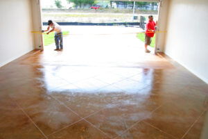 two men measuring inside garage with stained concrete